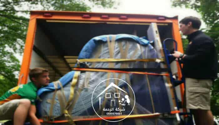 عاملان يحملان عفش الي سيارة نقل العفش